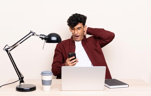 Jonge argentijnse man in een tafel met een laptop op zijn werkplek