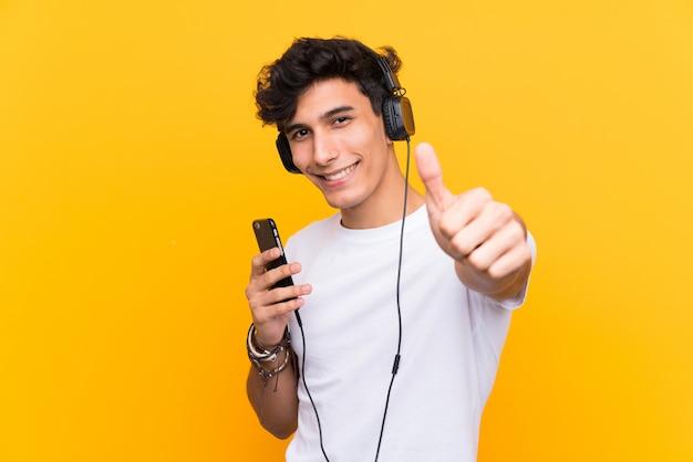 Jonge argentijnse man luisteren muziek met een mobiel over geïsoleerde gele muur