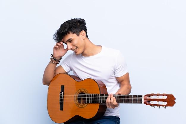 Jonge argentijnse man met gitaar over geïsoleerde blauwe muur heeft iets gerealiseerd en de oplossing voornemens