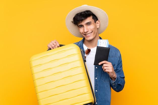 Jonge argentijnse man over geïsoleerde gele achtergrond in vakantie met koffer en paspoort