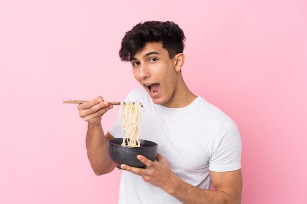 Jonge argentijnse man over geïsoleerde witte muur een kom noedels met stokjes houden en eten