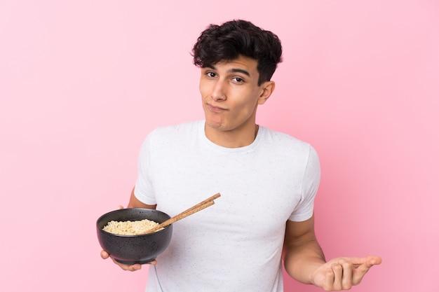 Jonge argentijnse mens over geïsoleerde witte muur die twijfelsgebaar maken terwijl het opheffen van de schouders terwijl het houden van een kom van noedels met eetstokjes