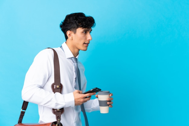 Jonge argentijnse zakenman over geïsoleerde blauwe muur