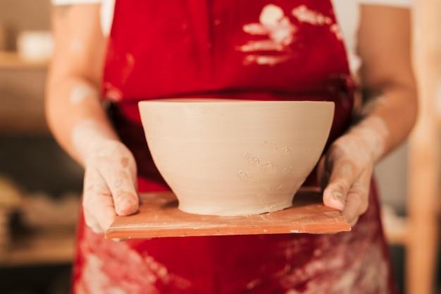 Jonge artisanale hand die een kom van de ambachtklei op houten dienblad toont