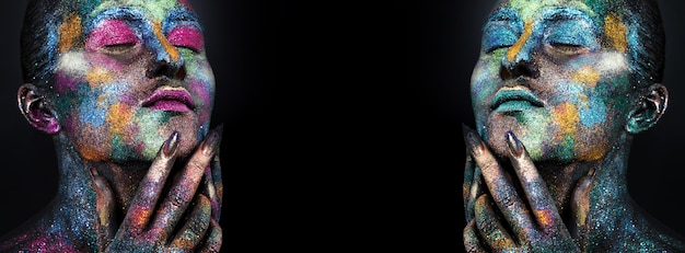 Jonge artistieke vrouw in zwarte verf en kleurrijke poeder. gloeiende donkere make-up. creatieve body art met als thema ruimte en sterren. bodypainting project: kunst, beauty, mode.