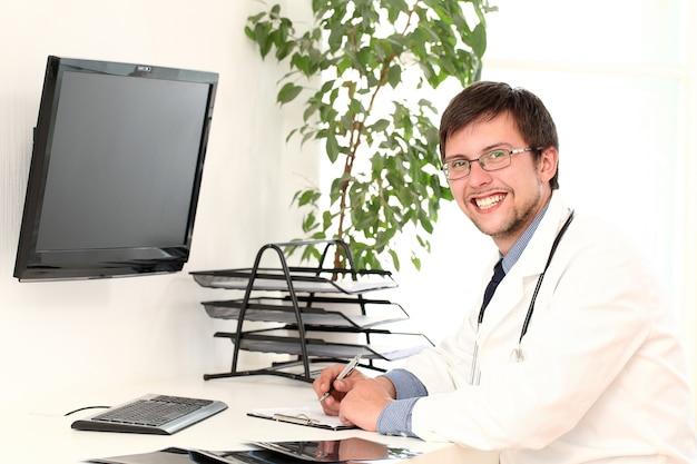 Jonge arts die in zijn bureau werkt