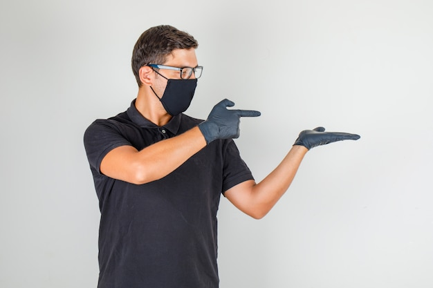 Jonge arts die vingers naar rechts in zwart poloshirt richten