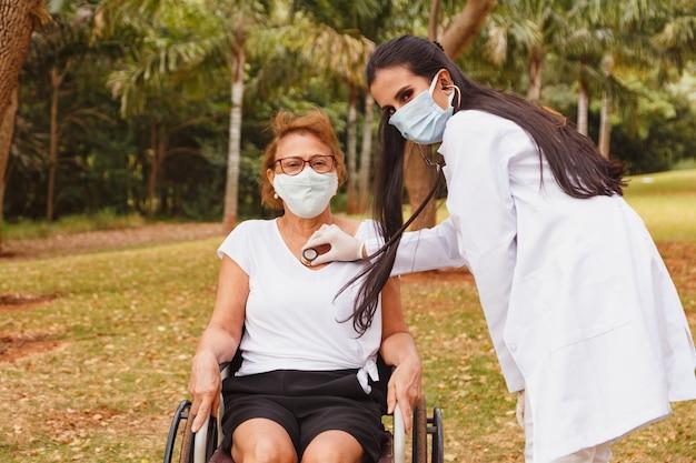 Jonge arts die voor een oudere vrouw in het park zorgt