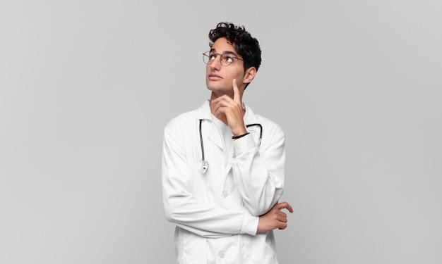 Jonge arts die vrolijk lacht en dagdroomt of twijfelt, opzij kijkend