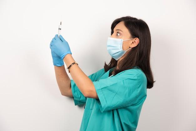 Jonge arts in medisch masker en handschoenen die spuit op witte achtergrond houden.
