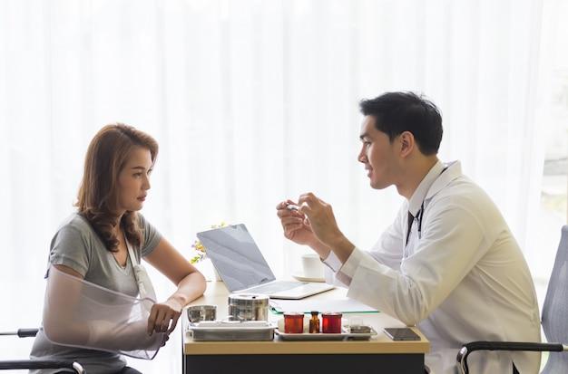 Jonge arts legde het letsel van een vrouwelijke patiënt in een gebroken arm in het kantoor van de arts uit.