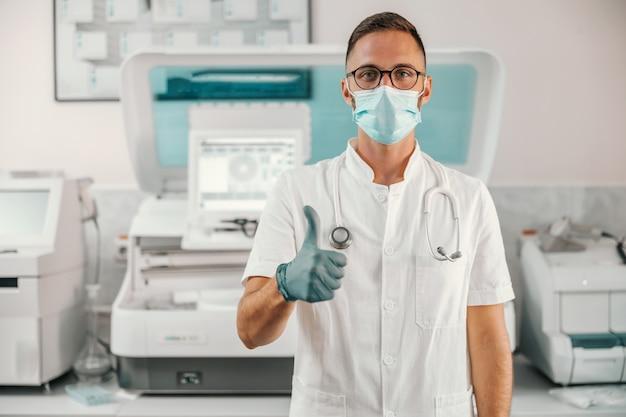 Jonge arts met rubberen handschoenen en gezichtsmasker staan in het ziekenhuis en duimen opdagen.