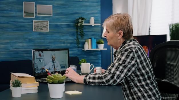 Jonge arts op afstand die webcam gebruikt die medicijnen voorschrijft aan zieke oude vrouw die in woonkamer zit v...