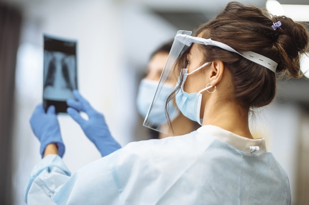 Jonge arts toont een röntgenfoto van de longen aan de patiënt en legt de diagnose uit. coronaviruspreventie en profylaxie. ziekenhuis en geneeskunde concept.