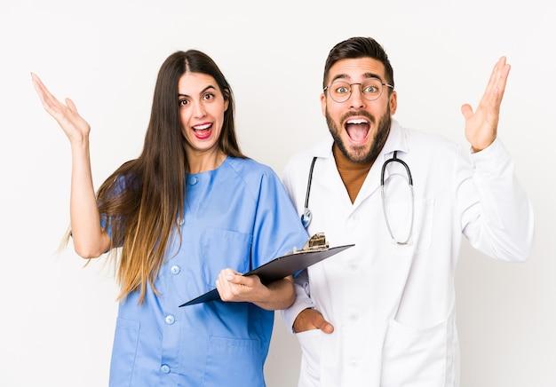 Jonge artsenman en een geïsoleerde verpleegster die een aangename verrassing ontvangen, opgewonden en handen opsteken.
