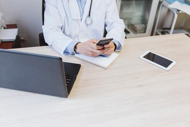 Jonge artsenmens die aan laptop bij het overleg werken. gebruik mobiele telefoon. modern medisch concept binnenshuis