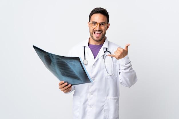 Jonge artsenmens die een radiografie houdt die op witte muur wordt geïsoleerd die telefoongebaar maakt
