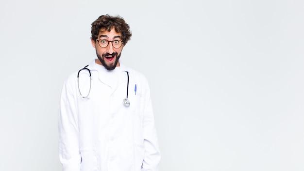 Jonge artsenmens die gelukkig en aangenaam verrast kijkt, opgewekt met een gefascineerde en geschokte uitdrukking over exemplaar ruimtemuur