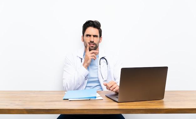 Jonge artsenmens die met zijn laptop over geïsoleerde muur een idee denken