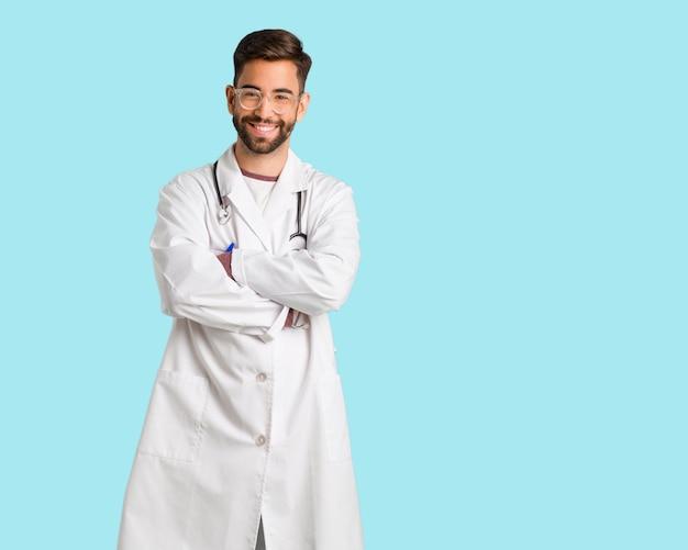 Jonge artsenmens die wapens kruisen, glimlachend en ontspannen