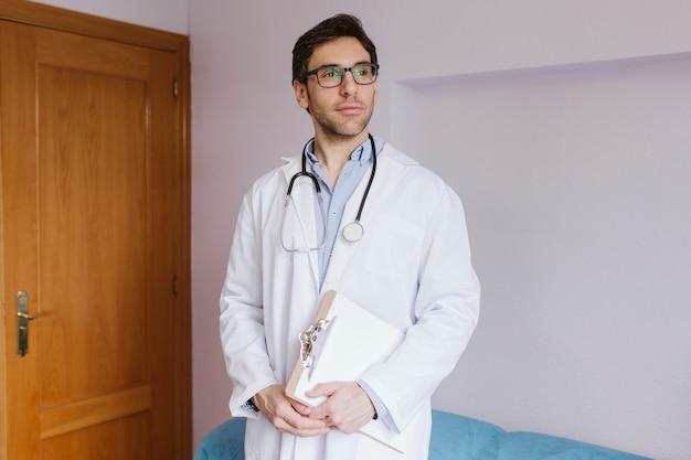 Jonge artsenmens die zich bij overleg bevindt. modern medisch concept binnenshuis