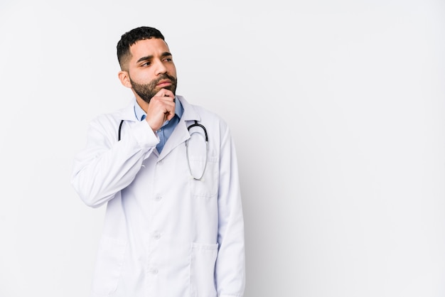 Jonge artsenmens die zijdelings met twijfelachtige en sceptische uitdrukking kijkt