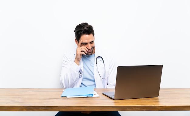 Jonge artsenmens met zijn laptop over het geïsoleerde muur lachen