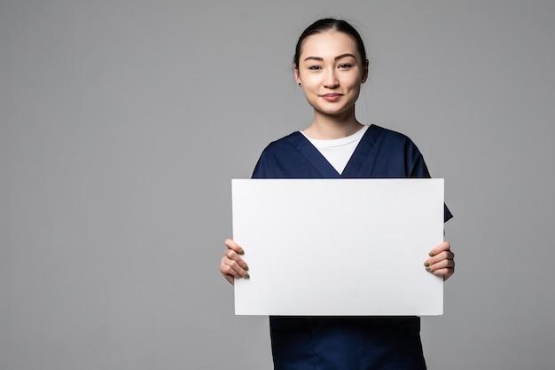 Jonge artsenvrouw die leeg aanplakbord toont, dat op witte muur wordt geïsoleerd