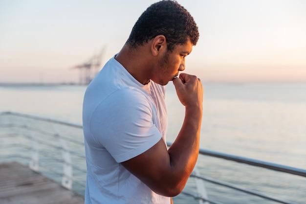 Jonge atleet die schaduwboksen beoefent op de pier