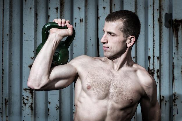 Jonge atleet die training doet met zware gewichten op de achtergrond van een grijze metalen wand