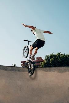 Jonge atleet die trucs op zijn fiets doet