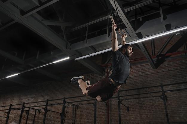 Jonge atleet doet pull-ups op gymnastische ringen bij cross fit gym. knappe man beoefenen van spier-ups swingende training oefening.