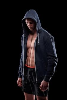 Jonge atleet in korte broek en uitgepakte hoodie die zich geïsoleerd over zwarte muur bevindt