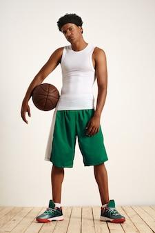 Jonge atleet in mouwloze witte korte, groene basketbalshort en sneakers met een vintage leren basketbal aan zijn zijde
