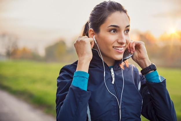 Jonge atleet jas aan te passen tijdens het luisteren naar muziek in het park