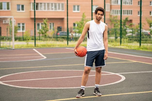 Jonge atleet met bal staande op circuit van basketbalveld in stedelijke omgeving