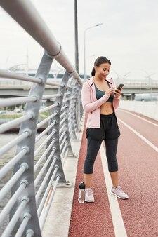 Jonge atleet sms't een bericht op mobiele telefoon tijdens sporttraining in frisse lucht