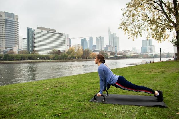 Jonge atletenvrouw die een opdrukoefening met opdrukoefeningstaven op het gras, dichtbij de rivier, op de achtergrond van de stad doen. sport- en trainingsconcepten