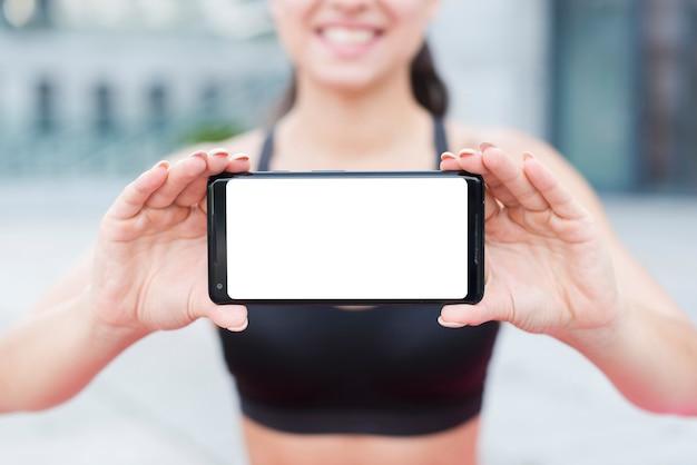 Jonge atletenvrouw met een smartphone