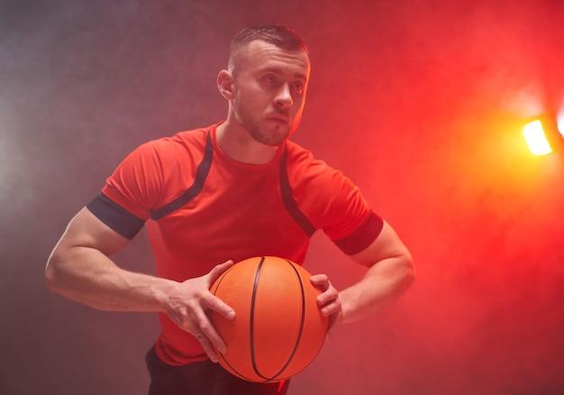 Jonge atletische basketbalspeler die zich voorbereidt op het gooien van de bal met achtergrondverlichting en rook