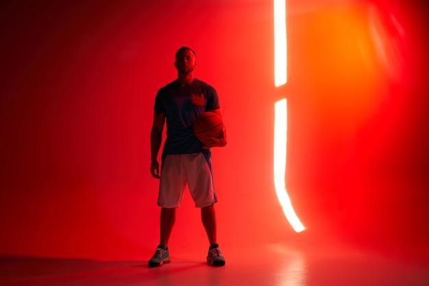 Jonge atletische basketbalspeler staat met de bal in de ene hand met achtergrondverlichting