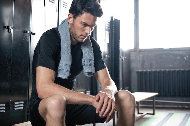 Jonge atletische blanke man zit alleen in de kleedkamer van de donkere sportschool en rust na de training.
