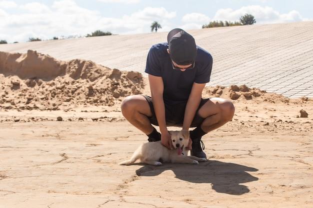 Jonge atletische jongen die zijn puppy aait die op het zand ligt.