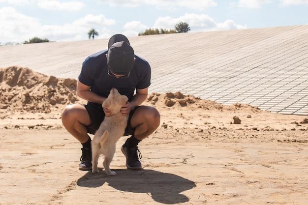 Jonge atletische jongen knuffelen en spelen met zijn puppy in het zand.