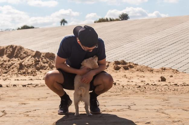 Jonge atletische jongen knuffelen zijn puppy in het zand.