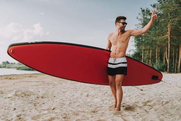 Jonge atletische kerel met branding die zich op strand bevindt.