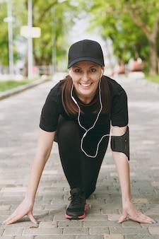 Jonge atletische lachende brunette vrouw in zwart uniform en pet met koptelefoon luisteren naar muziek bij lage start voordat ze rennen, trainen op pad in stadspark buitenshuis