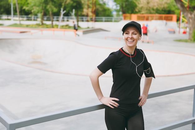 Jonge atletische lachende brunette vrouw in zwart uniform en pet met koptelefoon luisteren naar muziek, staan voor of na het hardlopen, trainen in stadspark buitenshuis