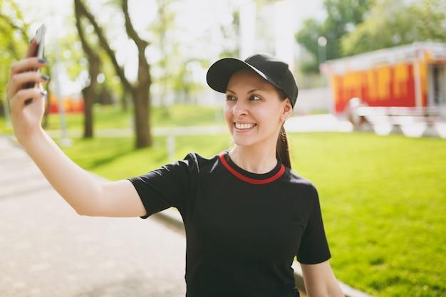 Jonge atletische lachende mooie brunette meisje in zwart uniform, pet op zoek op smartphone en selfie te doen op mobiele telefoon tijdens training in stadspark buitenshuis park