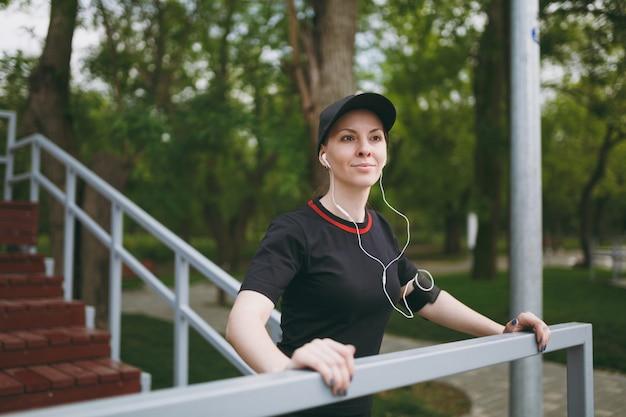 Jonge atletische lachende vrouw in zwart uniform en pet met koptelefoon luisteren naar muziek, rusten en staan voor of na het hardlopen, trainen in stadspark buitenshuis